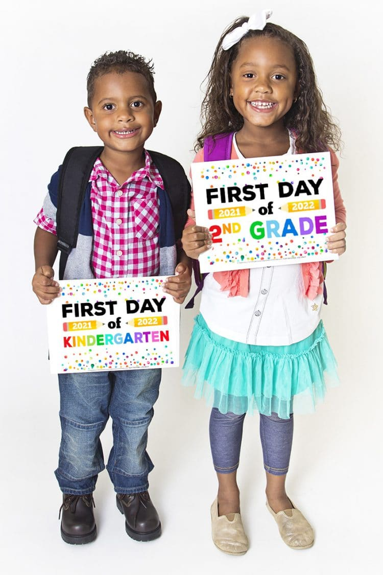 Two cute Black children holding up printable First Day of School Signs