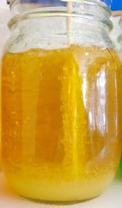 rock candy crystals developing on a stick in a mason jar of yellow sugar solution