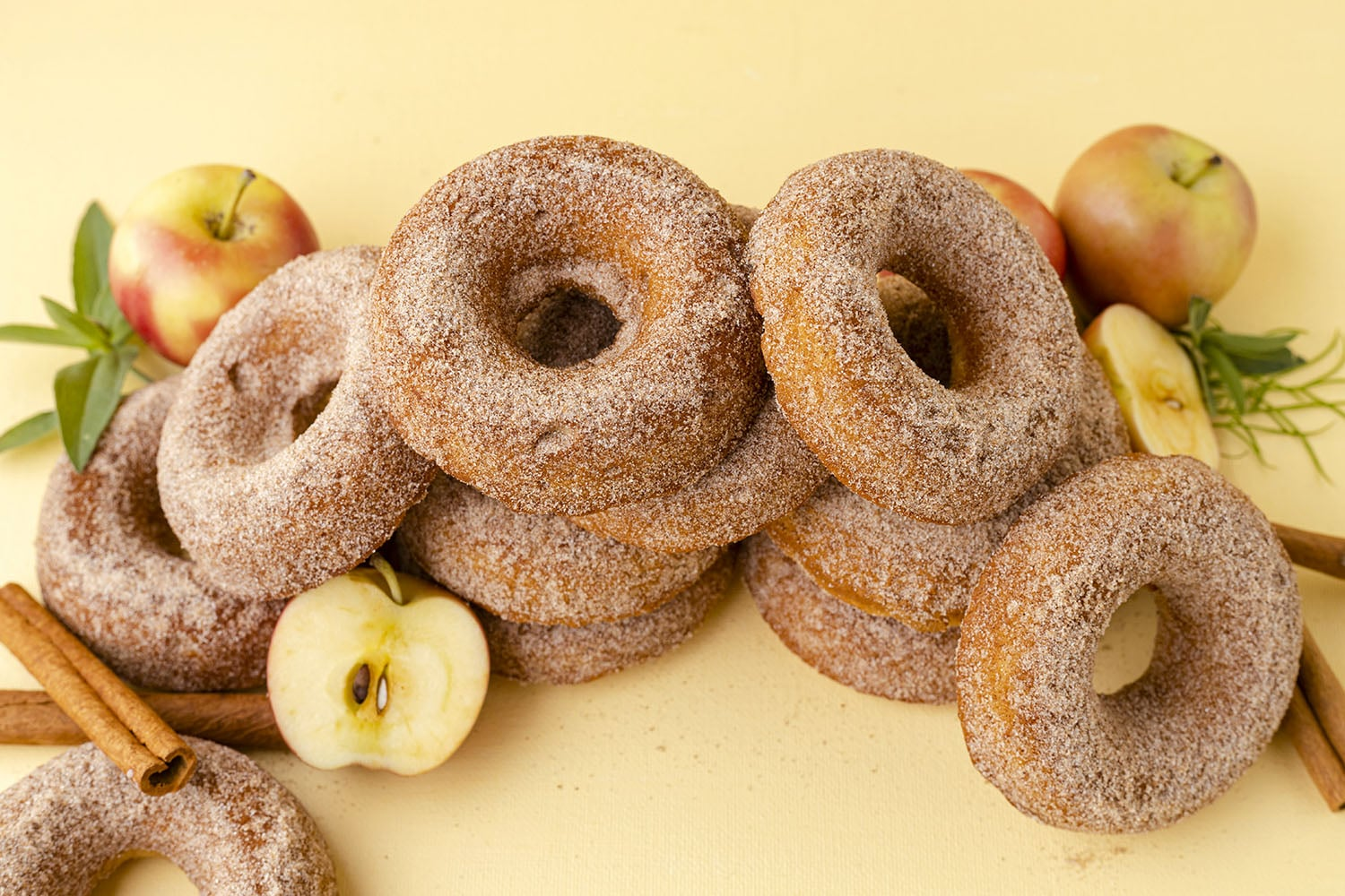 apple cider donuts in a stack with apples and cinnamon sticks on a yellow background