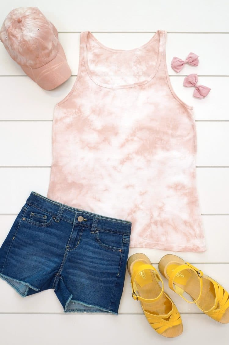 Blush pink tie-dye tank top and baseball hat made with avocado dye staged with an outfit on a white background