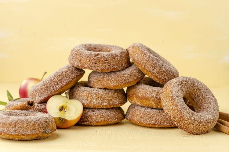 pile of apple cinnamon donuts on a yellow background with apples and cinnamon sticks