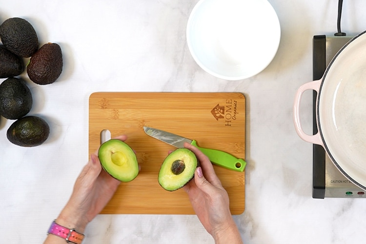 Hands holding a cut open avocado above cutting board with knife and pile of avocados