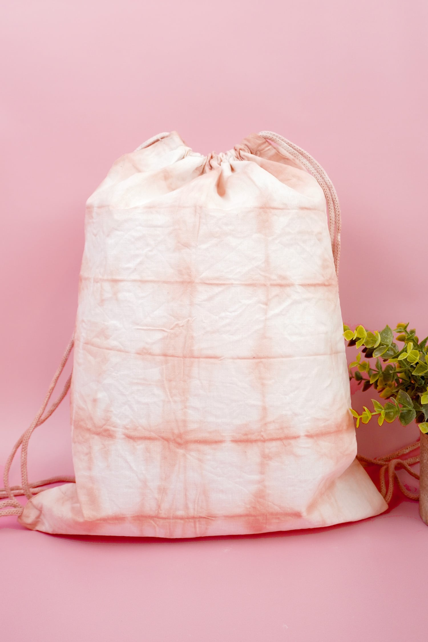 Blush pink Shibori tie-dyed drawstring backpack on pink background