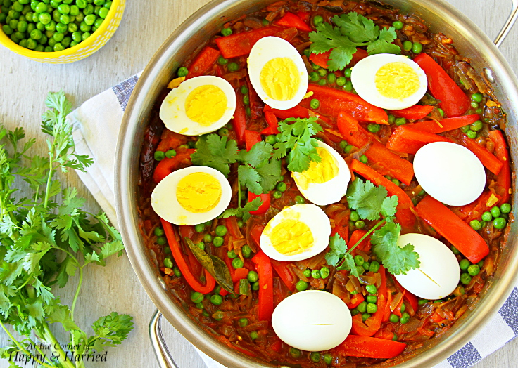 A delicious recipe of boiled eggs, red peppers and fresh green peas in a spicy gravy.