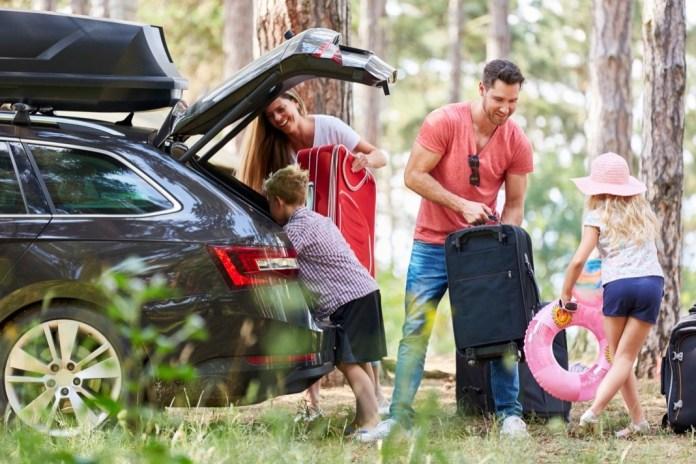 Kinder helfen Eltern beim Gepäcktragen zum Auto vor der Reise in den Urlaub.