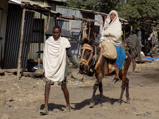 This photo shows a husband leading a donkey carrying his wife through the streets. Both people are wearing traditional dress