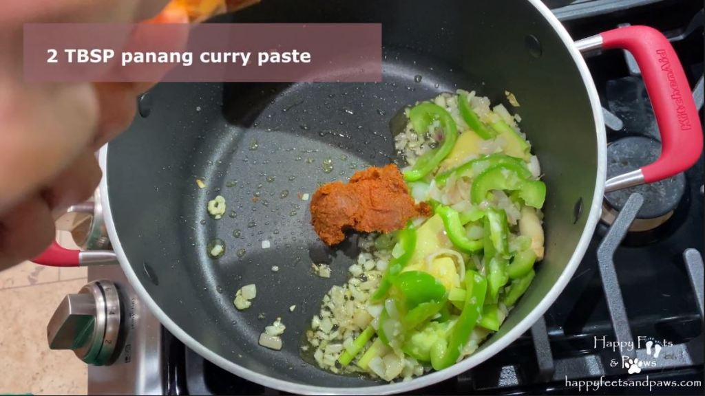 panang curry paste, ginger, green peppers in a pot cooking