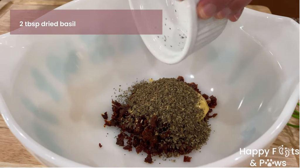 Adding dried basil to sun-dried tomato vinaigrette dressing recipe in bowl