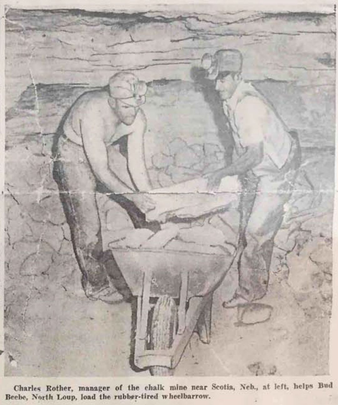 Charles Rother, manager of the chalk mine near Scotia, Neb, at left helps Bud Beebe, North Loup, load the rubber-tired wheelbarrow. Photo Credit: Omaha World Herald, Sept. 19, 1943