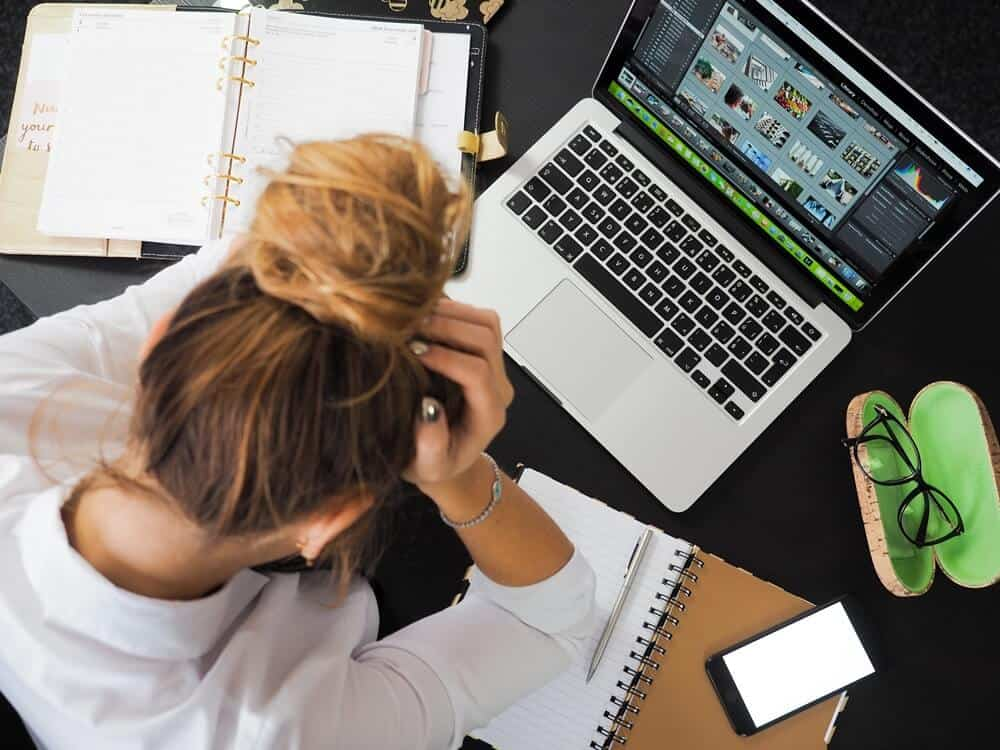 A woman stressed at her computer.