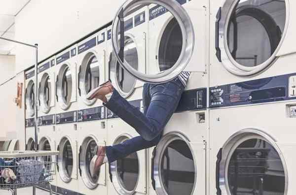 A woman hanging out of the dryer.