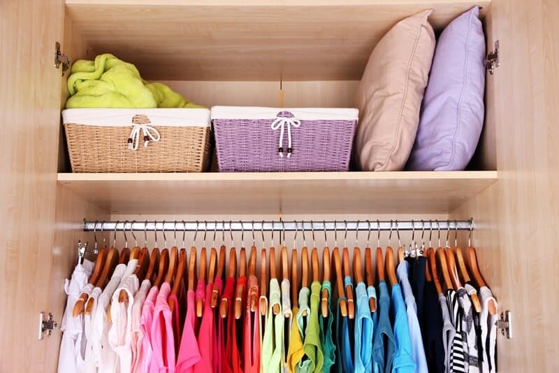 Colorful clothes hanging in a decluttered closet.