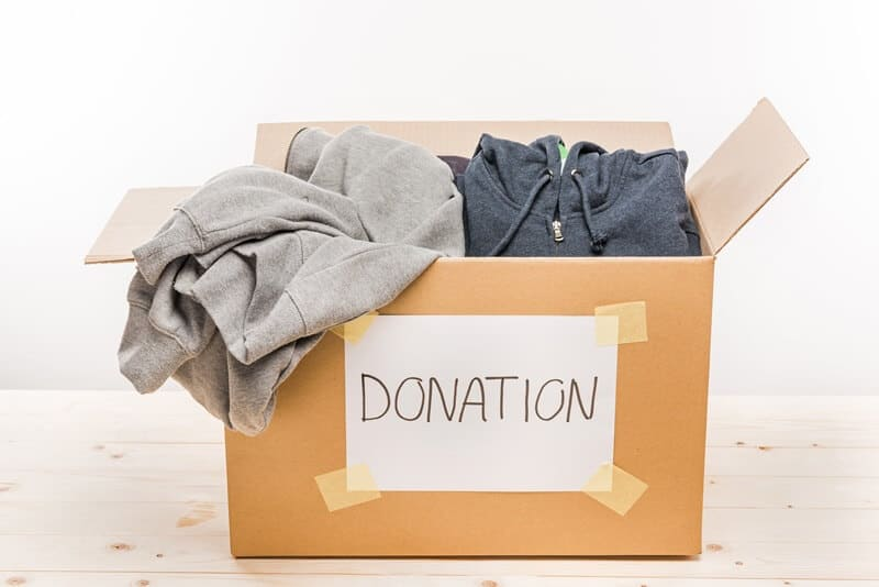 Donation box full of clothes from decluttering your bedroom.