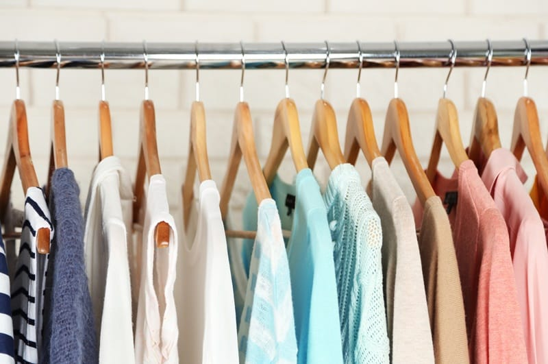 Capsule wardrobe clothes on wooden hangers