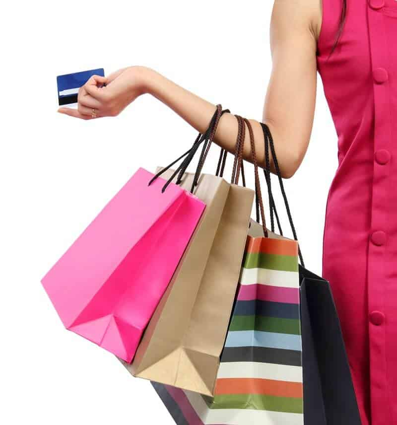 woman holding several shopping bags on her arm and a credit card