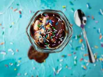 Ice cream sundae on a blue background with sprinkles everywhere