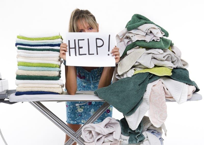 Woman behind a table covered with clothes to be ironed, displays a sign with help looking for laundry tips.