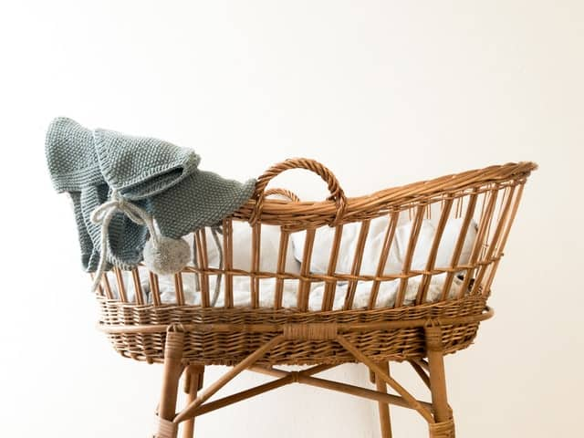 A woven bamboo baby bassinet with fluffy white blankets inside and a blue baby hat draped over the edge.
