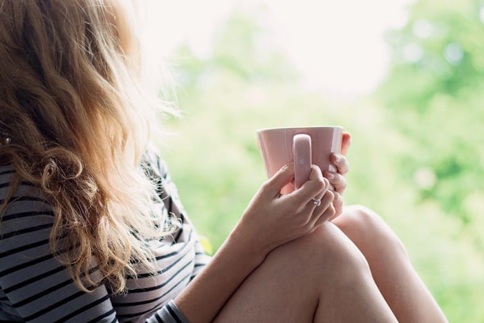 relaxed woman sitting holding a cup of tea