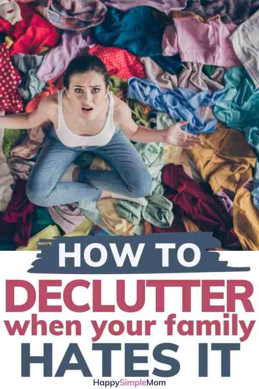 Pinterest Pin, woman looking up at camera while surrounded by clothing, wondering how she is going to get her family to help her declutter. Words on pin say How to declutter when your family hates it.
