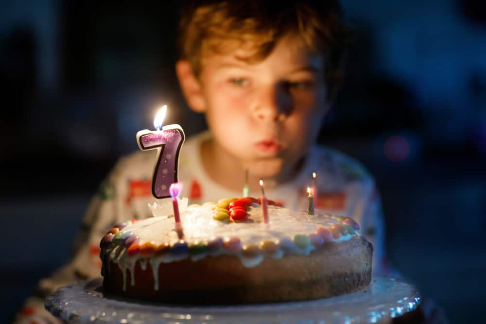 A little boy blowing out the candles on his home made cake for his seventh birthday.