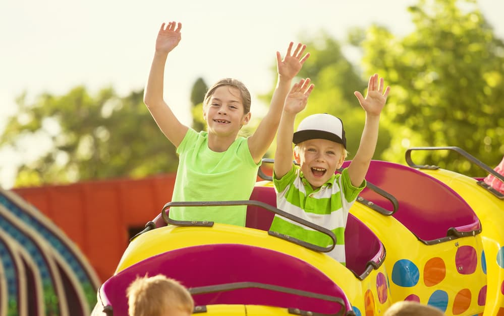 Brother and sister with their hands up on a kiddie roller coaster ride at a theme park.