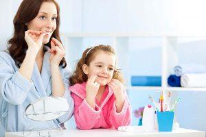 家長與小孩一同使用牙線清潔