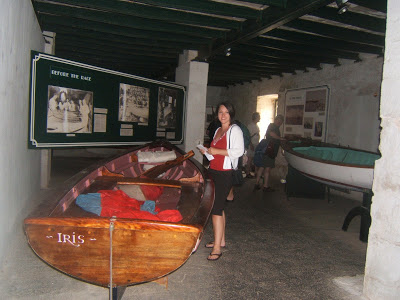 Woman next to a wooden boat in a museum