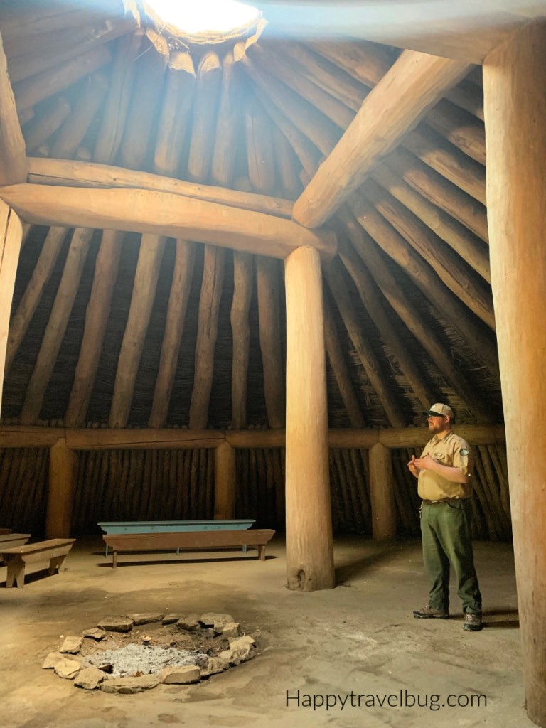 Inside the earth lodge with a park ranger. Large beams hold it together and the sun is shining through a hole in the top