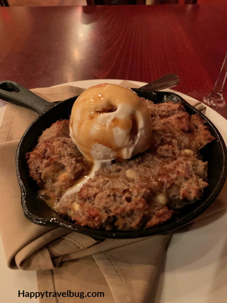 Pumpkin Spice bread pudding in a cast iron skillet with ice cream on top