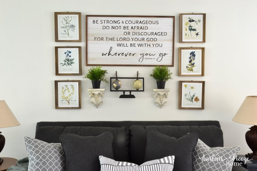 A gallery wall of pictures and other wall decor  behind a sofa