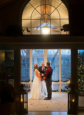 A wedding ceremony being performed in a sun room with rose petals scattered about the floor, as viewed through an open door and large clear window resembling the view into a chapel.