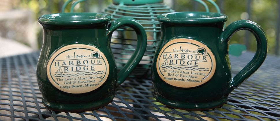 Green stonewear mugs with the Inn at Harbour Ridge logo