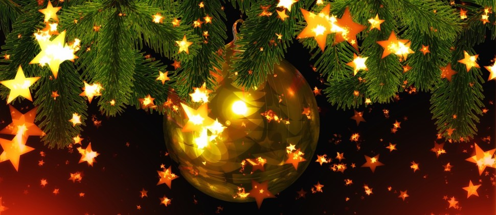 One large, shiny gold ornament dangling from an evergreen branch surrounded by gold twinkling lights