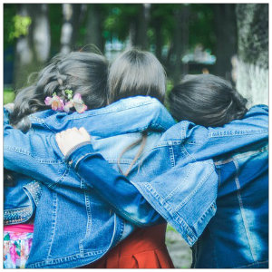 Three brunette girls wearing blue jean jackets huddled together with arms around each other