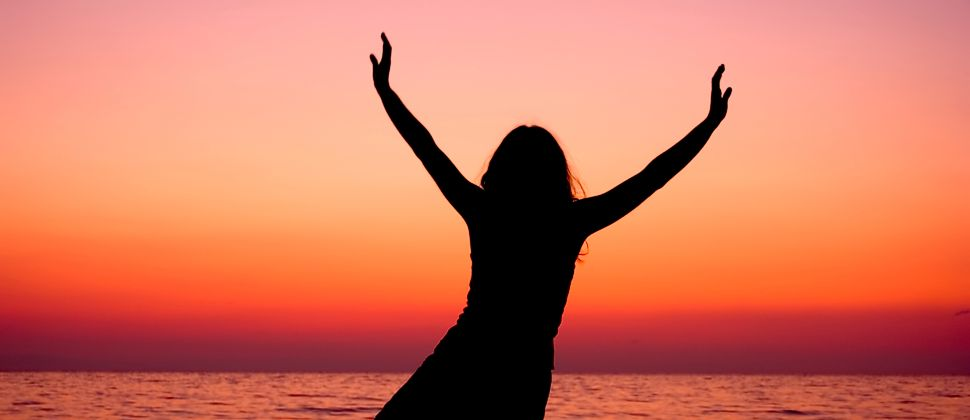 Woman throwing up hands in joy with red sunset and lake in background