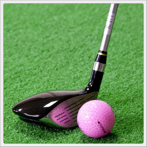 Black golf club next to a pink golf ball on green artificial turf