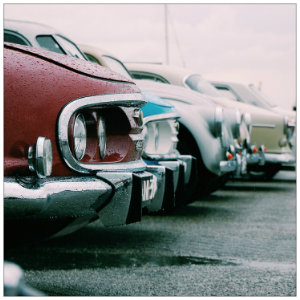 A row of red, silver, blue and green classic cars in a parking lot with grey skies