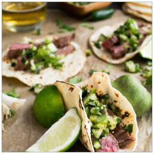 A table at a restaurant of white flour tacos with steak and slices of lime
