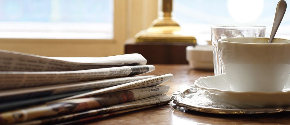 Newspapers and white coffee cup on desk with lamp
