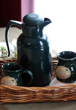 Green stoneware mugs and green coffee pot on wicker tray
