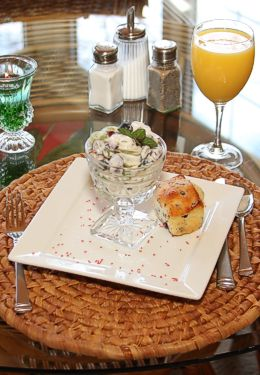 Breakfast table setting with goblet of orange juice on tan wicker placemat
