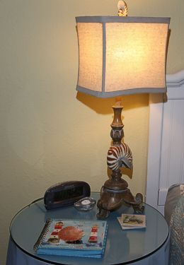 Side table with blue tablecoth, magazines and lit lamp with clock radio in a yellow room
