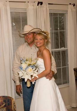 Blonde bride in wedding gown with groom in jeans and cowboy hat