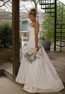 Blonde bride in white strapless gown with bouquet standing on edge of wooden porch