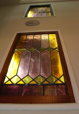 Stained glass window pink green and yellow in wooden frame