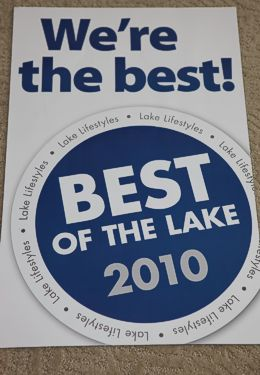 "Rectangular White sign with blue letters saying ""Best of the Lake 2010"" Award"