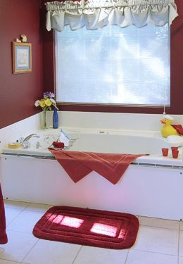 Large white tub for two with rubber ducky and mauve towels and mat