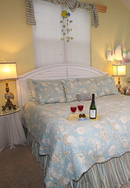 Blue quilted white wooden bed in cream colored walled room and lit lamps on side tables