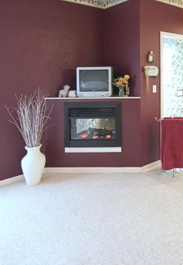 Fireplace surrounded by burgandy painted walls and TV on mantle